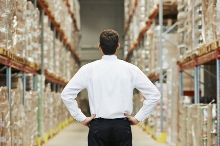 31776433 - male manager man standing in big modern warehouse with back towards viewer